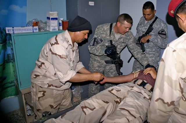 Soldiers with 3rd Battalion, 82nd Field Artillery Regiment, 2nd Advise and Assist Brigade, 1st Cavalry Division, U.S. Division-North, advise an Iraqi doctor and medics during a medical procedure near Joint Base Balad, Iraq, July 15, 2011.