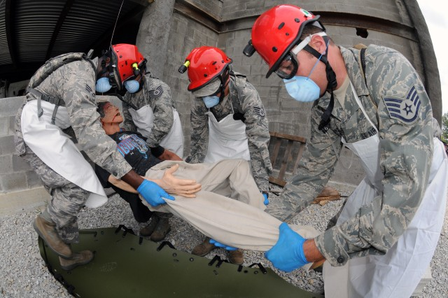 "MUSCATATUCK URBAN TRAINING COMPLEX, Ind. "" Air National Guard Fatality Search and Recovery Team members collect a simulated casualty from a collapsed parking garage here Aug. 18 and loads the casualty onto a sked as part of Vibrant Response 12, a U.S. Northern Command field training exercise conducted by U.S. Army North. (From left to right) Senior Airman Kevin Woodard, 123rd FSART, Ky. ANG; Tech. Sgt. Brittany Ingram, 123rd FSART, Ky. ANG; Staff Sgt. Jeffrey Feliciano, 156th FSART, P.R. ANG; and Staff Sgt. Jason Gallegos, 140th FSART, Colo. ANG. The multi-agency, multi-component exercise is part of Army North's mission to prepare federal military forces for their role in responding to a catastrophic chemical, biological, radiological or nuclear incident in the homeland."