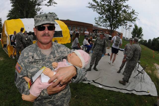"MUSCATATUCK URBAN TRAINING COMPLEX, Ind. "" Lt. Col. Gary Coffey, chaplain, West Virginia Chemical, Biological, Radiological, Nuclear and high-yield Explosives Enhanced Response Force Package, holds a simulated ""infant"" rescued from a collapsed parking garage Aug. 18. The West Virginia CERFP rescued casualties from the collapsed garage as part of Vibrant Response 12, a U.S. Northern Command field training exercise conducted by U.S. Army North here, at Camp Atterbury and various surrounding areas in Indiana. The multi-agency, multi-component exercise is part of Army North's mission to prepare federal military forces for their role in responding to a catastrophic chemical, biological, radiological or nuclear incident in the homeland."