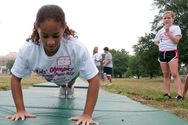 """Dara Alligood, 12, performs 56 """"airborne"""" pushups while her friendly """"rival,"""" Madison Bayne, right, watches at the Armed Services YMCA Kids' Olympics at Main Post Polo Field Saturday. Alligood is the daughter of Amy and Sgt. 1st Class Jesse English, Headquarters and Headquarters Battery, 2nd Battalion, 321st Field Artillery Regiment, 4th Brigade Combat Team, 82nd Airborne Division. Bayne is the daughter of Jenni and Sgt. 1st Class Joe Bayne, Headquarters and Headquarters Company, 16th Military Police Brigade."""