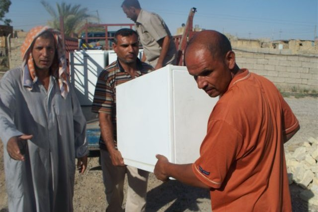 Iraqi men unload a refrigerator that was donated to local families by Baghdad-based service members Aug. 14, 2011. Service members collected small appliances that they no longer needed and were destined to be abandoned so that they might distribute to families in need.
