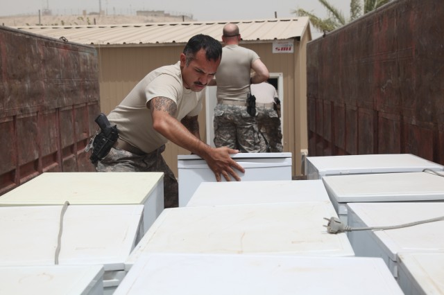Capt. Assad Raza, a civil affairs officer with Civil Affairs Team 665, Co. F, 96th Civil Affairs Battalion, currently assigned to Special Operations Task Force Central, helps to move a load of more than 80 refrigerators donated to local Iraqi families by Baghdad-based service members Aug. 9, 2011.