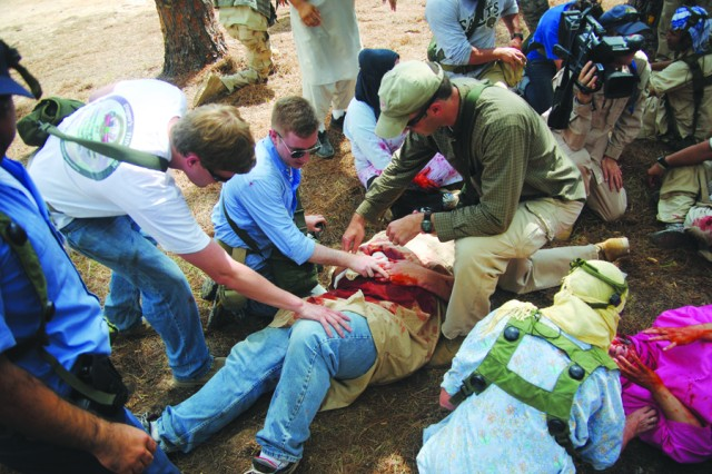 Brian Looser, (white t-shirt), a member of Illinois Rep. Judy Biggert's staff, Tom Stewart (blue shirt), a member of Iowa Rep. Leonard Boswell's staff, and Michael Walker (brown shirt) a member of Rep. Rodney Alexander's staff, treat a wounded Afghani during a scenario at one of the villages at Joint Readiness Training Center and Fort Polk. More than 40 staffers traveled to Fort Polk to see how Soldiers train before deploying to Iraq or Afghanistan.