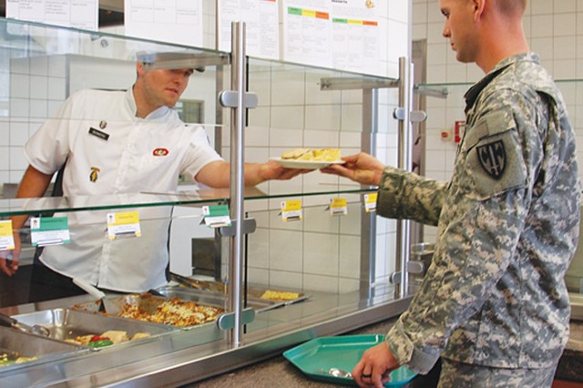 "Pvt. Kevin Keyes accepts a plate of food at the 1/10th SFG(A), Dining Facility on Panzer Kaserne, Germany, Aug. 11, 2011. Recently all DFACs in Europe began serving healthier foods and using ""Go for Green"" signs to indicate how each food affects Soldier performance, as part of the U.S. Army Europe ""Fueling the Team"" program."