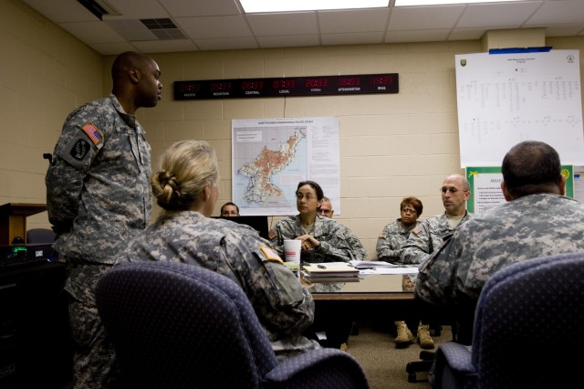 Maj. Leroy Carr III, answers questions from Col. Marion Garcia, the 200th Military Police Command's chief of staff and other staff members during a late meeting at the command's headquarters building on Fort Meade, Md. Carr, the deputy signal officer for the command, and other senior staff officers are coordinating efforts between command elements here and a forward team in Camp Walker, South Korea, during Ulchi Freedom Guardian 2011 -- a Combined Forces Command exercise involving the ROK, United States and seven United Nations Command sending state nations.