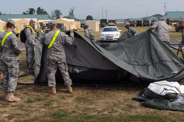"CAMP ATTERBURY, Ind. "" Soldiers from the 519th Military Police Battalion, Fort Polk, La., work together to set up a general purpose medium tent here Aug. 18, as part of Vibrant Response 12. The annual U.S. Northern Command field training exercise is conducted by U.S. Army North and is the command's largest disaster response exercise to date. This multi-agency, multi-component exercise is intended to prepare federal military forces for their role in responding to a catastrophic chemical, biological, radiological or nuclear incident in the homeland."