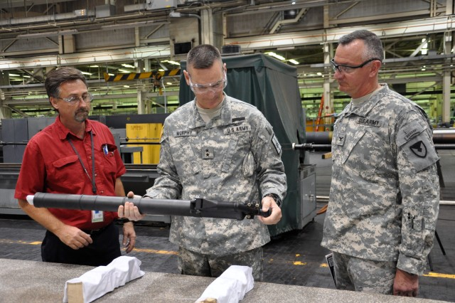 Arsenal General Foreman of Tubes Leon Rosko, left, briefs Maj. Gen. Patrick Murphy, center, about the Arsenal's new lightweight 60mm mortar production while Arsenal Commander Col. Mark Migaleddi looks on.