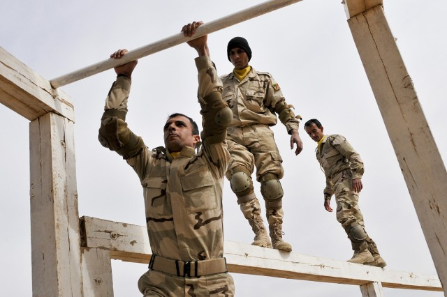 "After crossing elevated balance beams, Iraqi soldiers assigned to 4th Battalion, 21st Brigade, 5th Iraqi Army Division, scramble across monkey bars to finish an obstacle course at Kirkush Military Training Base, Iraq, March 12, 2011. Soldiers of Company A, 1st Battalion, 21st Infantry Regiment, 2nd Advise and Assist Brigade, 25th Infantry Division, taught the obstacle course, providing an opportunity for the Iraqi army soldiers to conduct physical fitness during the 25-day Tadreeb al Shamil, which is Arabic for ""All-Inclusive Training,"" training program at KMTB. Tadreeb al Shamil is an Iraqi military initiative aimed at bolstering the IA's national defense capabilities prior to the end of Operation New Dawn."