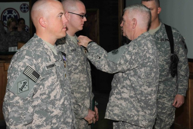 (RIGHT) Brig. Gen. Don S. Cornett Jr., commanding general of the 310th Expeditionary Sustainment Command, and an Aurora, Neb., native, pins the Purple Heart and Combat Action Badge onto Spc. Matthew Keeler, a public affairs specialist with the 109th Mobile Public Affairs Detachment, 310th ESC, and a Ridley, Pa., native, during an awards ceremony in the 310th ESC's joint Operations Command on Joint Base Balad, Iraq. (U.S. Army photo by Sgt. 1st Class Kevin Askew)