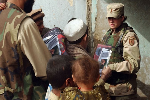 Staff Sgt. Jen Brooks, with the Kandahar Provincial Reconstruction Team, gives candy to students from the Abdul Karzai Middle School in Khandahar, Afghanistan, Sept. 14, 2004.