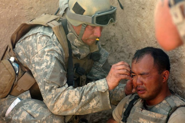 A Special Forces team medic with Combined Joint Special Operations Task Force - Afghanistan treats another U.S. Soldier for shrapnel wounds he received from a rocket-propelled grenade explosion while battling Taliban in the Sangin District, April 10, 2007. The Soldier continued fighting minutes after he was treated.