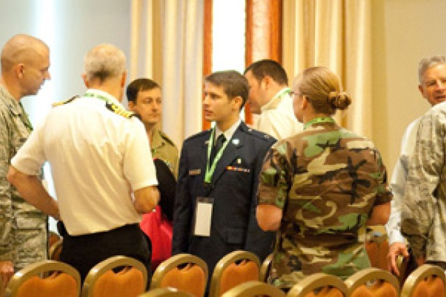Attendees of the 2011 Advanced Technology Applications for Combat Casualty Care Conference continue the discussion following a presentation. The Conference included more than four days of insightful and relevant plenary and didactic sessions on topics such as pre-hospital care, wound care, and military human performance.