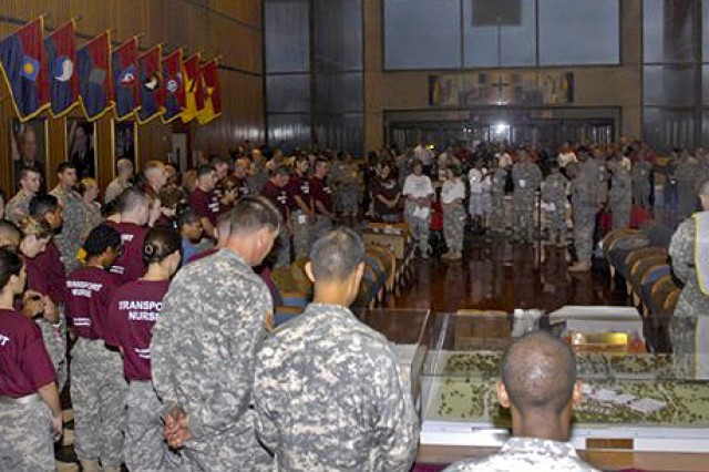 Soldiers bow their heads in prayer before they move inpatients from Walter Reed Army Medical Center in Washington, D.C., to the National Naval Medical Center in Bethesda, Md., Aug. 27, 2011. Officials moved up the transfer date by one day to avoid the worst effects of Hurricane Irene along the East Coast.