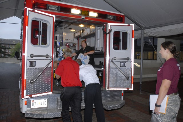 Soldiers and civilians load the first inpatient is loaded up into an ambulance for transport from Walter Reed Army Medical Center in Washington, D.C., to the National Naval Medical Center in Bethesda, Md., Aug. 27, 2011.