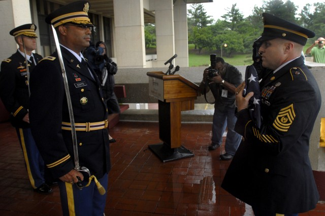Army Col. Norvell D. Coots, left, receives the U.S. flag from Command Sgt. Maj. Rodolfo R. Delvalle at Walter Reed Army Medical Center in Washington, D.C., Aug. 27, 2011. Coots is Walter Reed Health Care System's commander,and Delvalle is Walter Reed's command sergeant major.