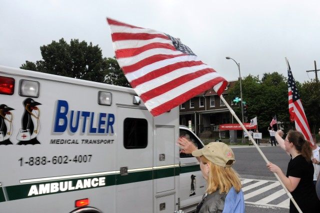 Heather Wilk, a former Army medic, waves to the departing Soldiers as her daughter, Kimberly Hockman, a Navy veteran, waves the American flag as one of the last wounded warriors is transported to the National Naval Medical Center, Bethesda, Md.