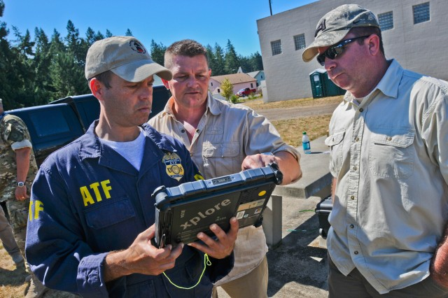 Brennan Phillips, an explosives enforcement officer with the Bureau of Alcohol, Tobacco, Firearms and Explosives, gets familiar with a newly developed unmanned aerial vehicle device Aug. 25 at Leschi Town, the premier training mock village on Joint Base Lewis McChord, Wash., during a live-fire Explosive Ordnance Disposal exercise on JBLM Aug. 24-26, called Ravens Challenge, that brought together military and civilian bomb techs from across Washington State and even agencies from Portland, Ore., and British Columbia, Canada. The event also welcomed scientists from the Albuquerque, N.M.-based Sandia National Laboratories and a variety of companies across the country promoting new technology that supports the EOD community.