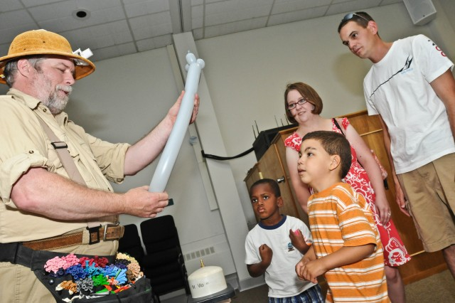 Five-year-old Cameron Spray watches with eager eyes as Roger Lander, a balloon artist who calls himself the Balloon Buffoon, makes an alien for him Aug. 26, 2011, at the Chapel Support Center on McChord Field, Wash., during a back-to-school carnival event for families with children enrolled in the Exceptional Family Member Program. The event provided entertainment for the kids and an abundance of information for the adults from a wide array of support services on Joint Base Lewis-McChord, Wash.