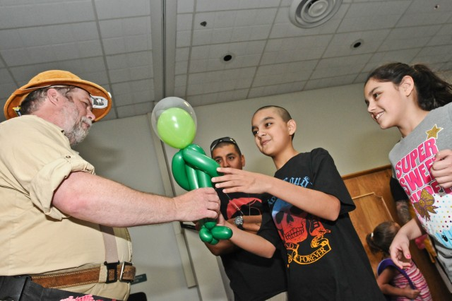 Eleven-year-old Joshua Onate delightfully eyes a balloon alien Roger Lander, a balloon artist who calls himself the Balloon Buffoon, made for Onate Aug. 26, 2011, at the Chapel Support Center on McChord Field, Wash., during a back-to-school carnival event for families with children enrolled in the Exceptional Family Member Program. The event provided entertainment for the kids and an abundance of information for the adults from a wide array of support services on Joint Base Lewis-McChord, Wash.