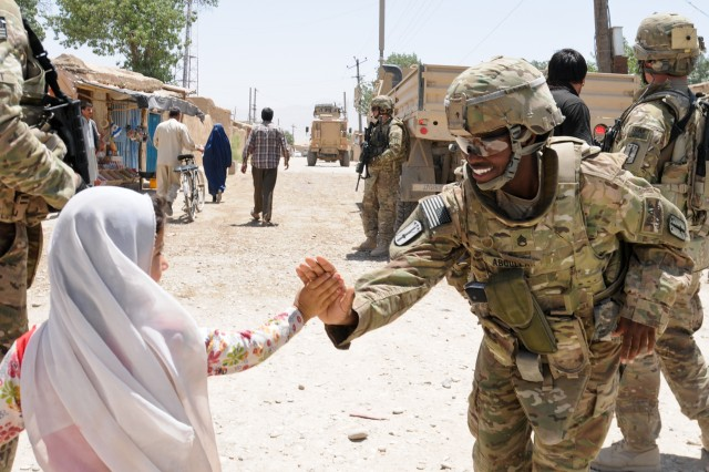 Staff Sgt. Samira Abdullahmuhammad with a female engagement team, 40th Engineer Battalion, 170th Infantry Brigade Combat Team, gives a high-five to a child during a mission to deliver medical supplies to a clinic in Deh Dadi, Afghanistan, June 1, 2011.