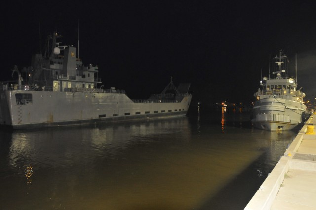Army Logistic Support Vessel-1, the Gen. Frank S. Besson Jr. (left) prepares to berth at Fort Eustis' 3rd Port the night of Aug. 28 upon return from the Patuxent River in southern Maryland. Army watercraft embarked the port the evening of Aug. 26 setting sail for safe haven due to the arrival of Hurricane Irene.