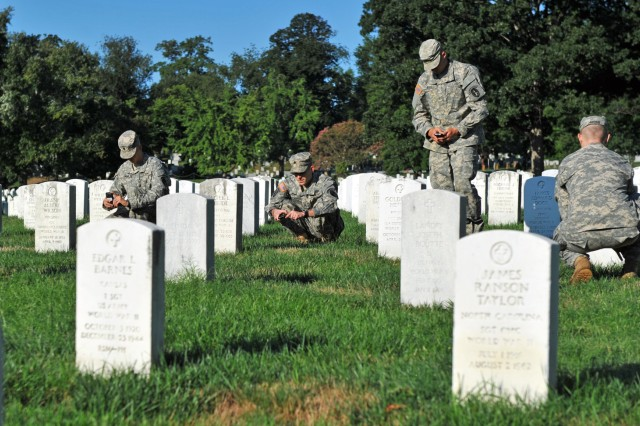 3rd U.S. Infantry Soldiers of Delta Company photograph headstones at Arlington National Cemetery in Virginia with smartphones to check burial locations against burial records.
