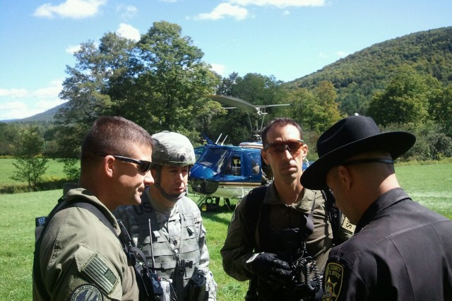 Lt. Col. Albert Thiem (center), of Ballston Spa, N.Y., Greene County Deputy Sheriff J.R. DelVecchio (right), and two New York State Police helicopter pilots coordinate the rescue of civilians trapped by Hurricane Irene floodwaters. Thiem belongs the New York Army National Guard's 42nd Infantry Division.