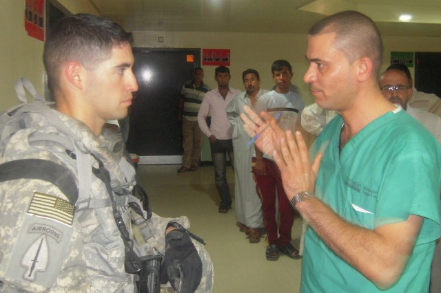 Capt. Michael De La Vega, the squadron physician's assistant for 6th Squadron, 9th Cavalry Regiment, 3rd Advise and Assist Brigade, 1st Cavalry Division, and a doctor from Al Zahraa hospital in Al Kut, Iraq, discuss their individual backgrounds and treating of patients on Aug. 20, 2011.