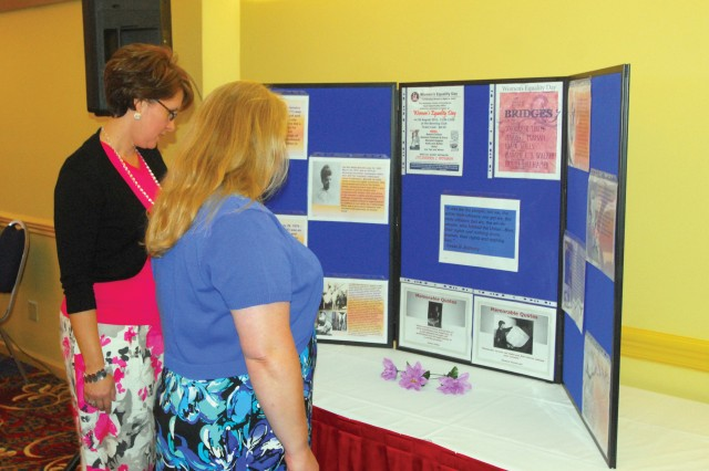 "Chelle James, left, and Jackie McClaflin look at an Equal Opportunity Office display about the women's suffrage movement. Biographies and quotes "" including those listed here "" from American women of different backgrounds were on display during the luncheon."