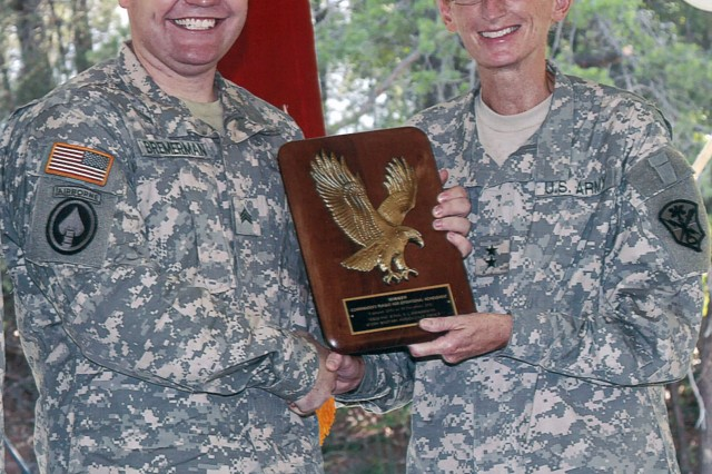 Sgt. Joshua Bremerman (left), of the 204th Military Intelligence Battalion, receives the Commander's Plaque for Operational Achievement, from Maj. Gen. Mary Legere, commanding general of Intelligence and Security Command (INSCOM), at Fort Belvoir, Va., July 21. (U.S. Army photo by Robert J. Bills, Headquarters INSCOM)
