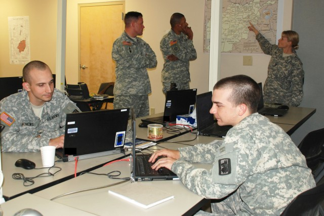 Two Soldiers of the 14th Military Intelligence Battalion analyze intelligence (foreground) while others familiarize themselves with a map of Afghanistan Aug. 17 during a Military Rehearsal Exercise at the Intelligence and Security Command Detention Training Facility on Camp Bullis. The battalion spent a week validating its readiness to accomplish its interrogation mission when deployed in support of Operation Enduring Freedom. (U.S. Army photo by Gregory Ripps)