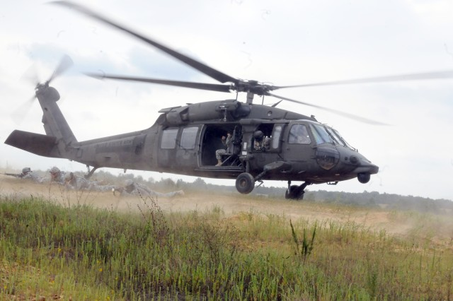 Soldiers from the 19th Engineer Battalion prepare for takeoff in a UH-60 Blackhawk helicopter while others pull security during the battalion's air assault operations training on Aug. 25. The training taught Soldiers the proper method of establishing landing zone security and preparing casualties for medical evacuation. (U.S. Army photo by Sgt. Michael Behlin)