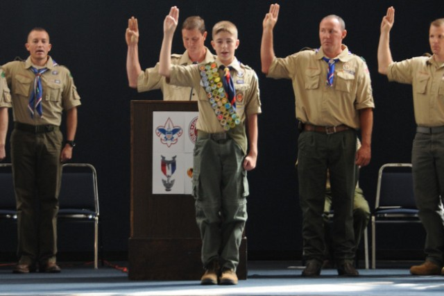 Joshua Halverson, standing in front of the podium, joins the ranks of fellow Eagle Scouts by reciting the Eagle Scout oath at his court of honor Sunday.