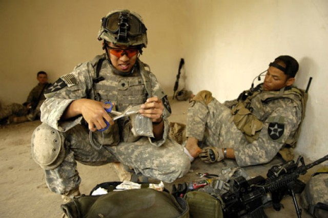 Spc. Kon Im, a medic, treats Staff Sgt. Alec Rubenstein. Rubenstein was  injured by a fragment of metal during a cordon and search operation in Baquba, Iraq, April 2, 2007.