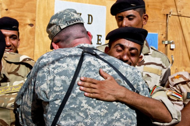 Staff Sgt. Richard Thomas congratulates an Iraqi soldier graduating from an equipment training course on Joint Security Station Al Rashid in Baghdad, Oct. 7, 2010. Thomas, who helped instruct the Iraqi soldiers, is an armor crewman assigned to 3rd Battalion, 69th Armor Regiment, 1st Advise and Assist Brigade, 3rd Infantry Division.