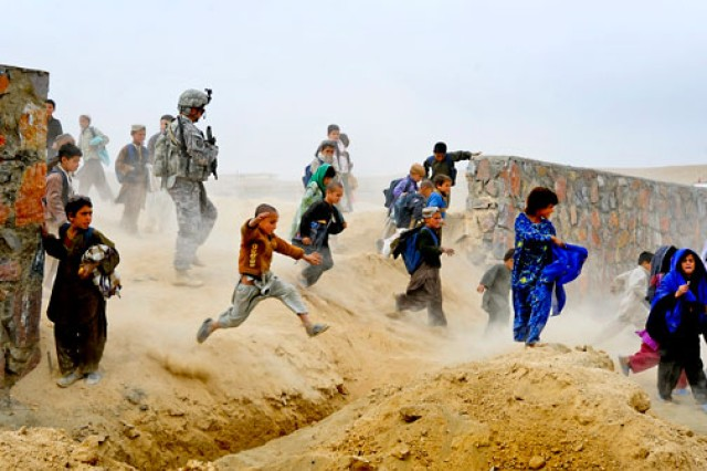 (Above) Escorted by dozens of children, Sgt. 1st Class Jeff Cesaitis exits the site of a future park in Qalat, Afghanistan, during a site visit, Oct. 28, 2010. Cesaitis was assigned to Provincial Reconstruction Team Zabul's security force.