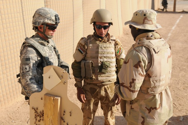 Staff Sgt. Joshua Moody, squad leader with Company B, 1-5 Cavalry, 2nd Brigade Combat Team, 1st Cavalry Division, advises an Iraqi soldier on the range during a week of marksmanship training on an Iraqi Military Post, Aug. 16, 2011. The Iraqi soldiers are learning basic marksmanship, close quarters marksmanship, advanced marksmanship and how to enter and clear a room in an urban environment.
