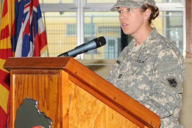 Capt. Terri Mason, U.S. Army Africa's Headquarters Support Company incoming commander speaks to troops during a change of command ceremony Aug. 31 at Caserma Ederle's Teen Center, where she took the reins of command from Maj. Brian Hanley.