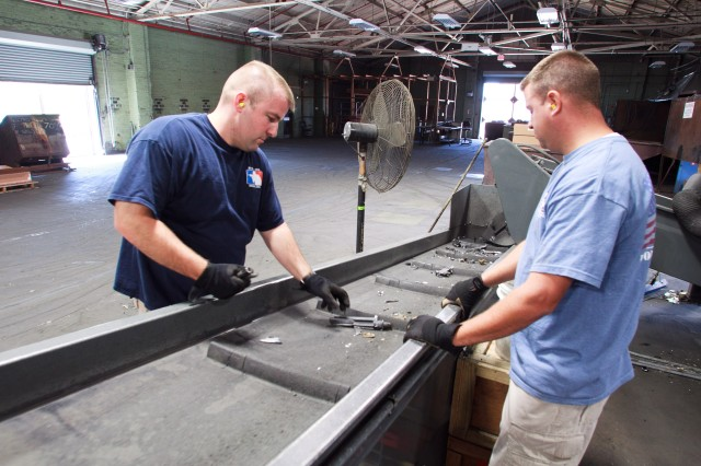 Alan George, right, and Jerrod Kirkpatrick of DLA Disposition Services, watch the mangled pieces of M16s as they flow out of Captain Crunch onto the conveyor belt. Any pieces not properly destroyed are returned to the shredder.