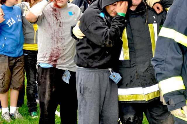 """The """"injured"""" are helped to a decontamination area after being exposed to a chlorine gas leak."""