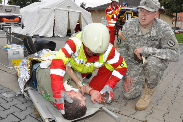 Chaplain (Capt.) Andrew Shriver works with a host nation first responder while offering spiritual support during a force protection exercise on Wiesbaden Army Airfield.