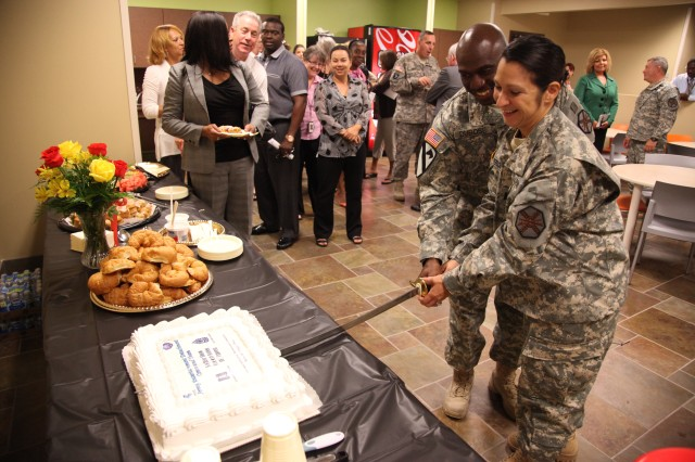 Capt. Yvonne Perdomo and First Sgt. Johnny Dubose cut cake following the ceremony in which Capt. Perdomo assumed command of the Army Entertainment Detachment on Thursday, Sept. 1, 2011. (US Army Photo)