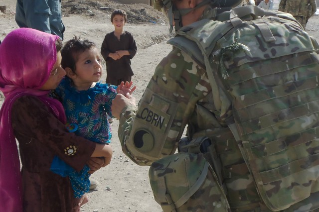 Sgt. 1st Class Elizabeth Jackson stops to say hello to a young child during a foot patrol through the bazaar in Qalat, Zabul province, Afghanistan, Aug. 21, 2011.