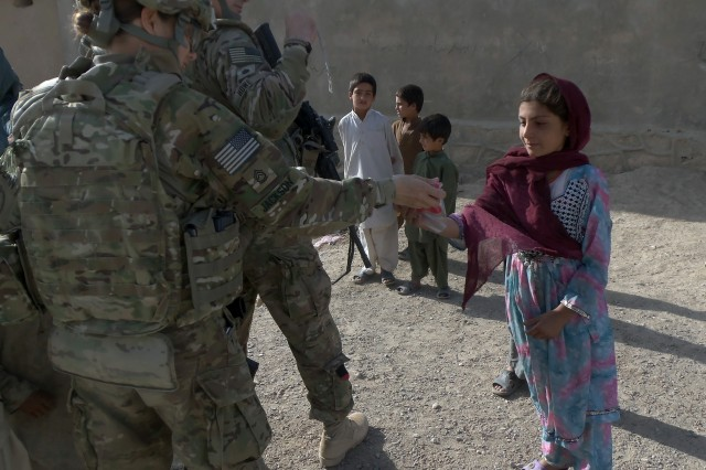 Sgt. 1st Class Elizabeth Jackson hands out shoes and toys to children at the Qalat bazaar during a foot patrol in Zabul province, Afghanistan, Aug. 21, 2011.