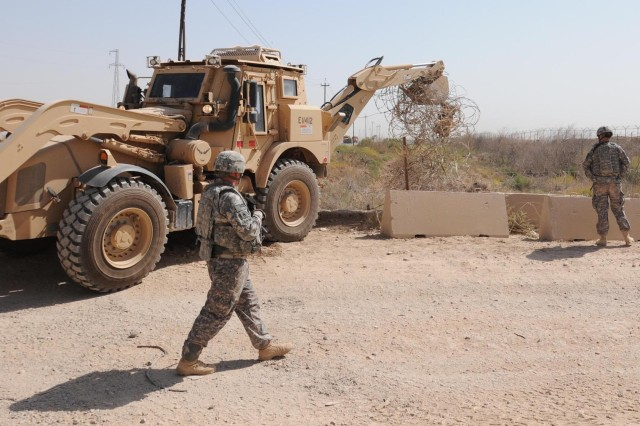 Soldiers from Company C, 2nd Special Troops Battalion, 2nd Advise and Assist Brigade, 1st Cavalry Division, U.S. Division - North, removes excess concertina wire from the Septia Canal with a backhoe outside of Contingency Operating Base Warhorse, Iraq, Aug. 29, 2011.