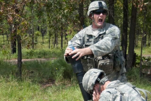 """A mortarman with 1st Brigade Combat Team, 82nd Airborne Division, shouts back the command of """"fire"""" to his section leader before releasing an 81mm mortar into a mortar tube to be fired during a walk-and-shoot field exercise on Fort Bragg, N.C., August 16, 2011.  Exercises like these instill confidence in the abilities of mortar and artillery support to provide accurate and effective fire when needed."""