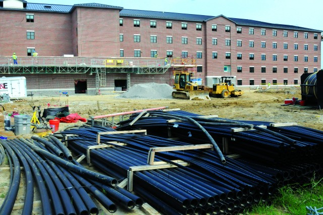 The black piping in the foreground will be used for a network of wells in a geothermal system that will heat and cool this barracks in the background at Fort Lee, Va.