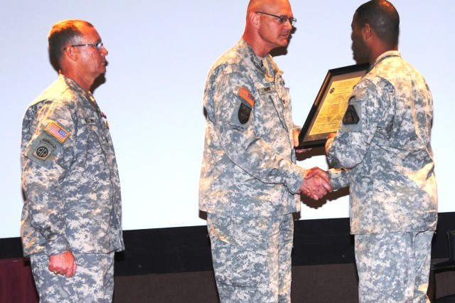 Col. William C. Hoppe, former project manager for Warfighter Information Network-Tactical (PM WIN-T), (center) handed the Product Manager Command Post Systems and Integration (PdM CPS & I) charter to Lt. Col. Carl J. Hollister (right), the new PdM for CPS & I, during a July 15 change of charter ceremony at Redstone Arsenal, Ala. Lt. Col. Terry Wilson, outgoing product manager, stood to the left. (U.S. Army photo)