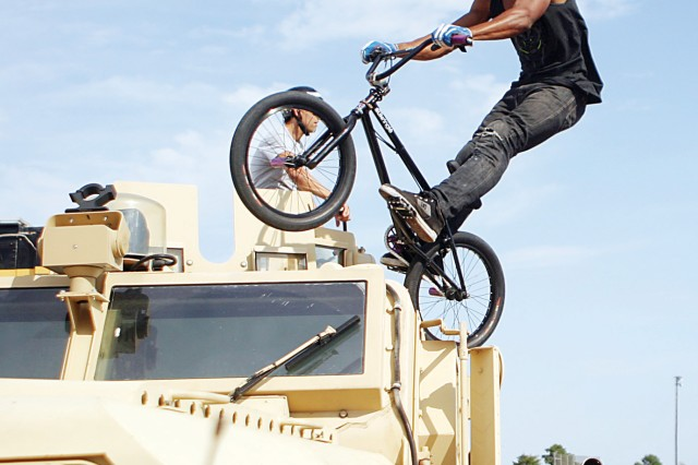 Mykel Larrin, professional BMX rider, Bikes Over Baghdad, stalls on a military vehicle during the group's performance as part of the Warrior Zone grand opening celebration Aug. 26 in the Warrior Zone parking lot, Fort Riley, Kan. Bikes Over Baghdad is a group of about 10 BMX athletes who travel to Iraq to perform for the troops.