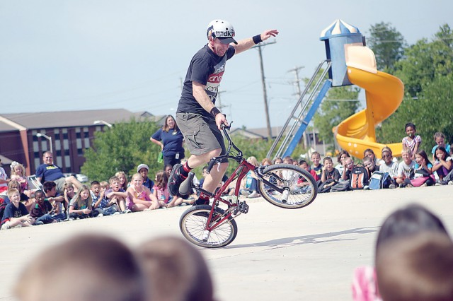 Scott Powell, BMX professional, Bikes Over Baghdad, shows off flatland tricks Aug. 24 during a demonstration at Custer Hill Elementary School, Fort Riley, Kan.